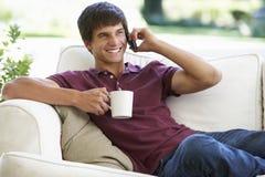 Adolescente que habla en móvil mientras que lleva a cabo la bebida Fotos de archivo libres de regalías