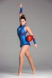 Adolescente que hace danza de la gimnasia con gimnástico rojo Imagen de archivo libre de regalías