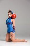 Adolescente que hace danza de la gimnasia con la bola gimnástica roja Fotografía de archivo