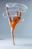 Adolescente que hace danza de la gimnasia con la cinta blanca en una parte posterior del azul Foto de archivo