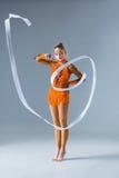 Adolescente que hace danza de la gimnasia con la cinta blanca en una parte posterior del azul Foto de archivo libre de regalías