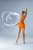 Adolescente que hace danza de la gimnasia con la cinta blanca en una parte posterior del azul Imagen de archivo libre de regalías