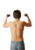 Adolescente que hace ejercicios con pesas de gimnasia. Foto de archivo