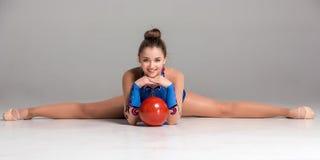 Adolescente que hace ejercicios de la gimnasia con rojo Imagen de archivo libre de regalías