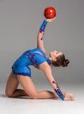 Adolescente que hace ejercicios de la gimnasia con rojo Imagenes de archivo