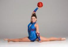 Adolescente que hace ejercicios de la gimnasia con rojo Fotos de archivo
