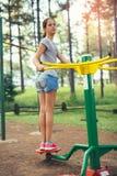 Adolescente que hace ejercicios en el simulador Imagen de archivo