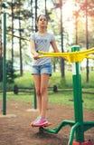 Adolescente que hace ejercicios en el simulador Foto de archivo