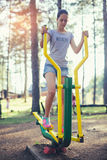 Adolescente que hace ejercicios en el simulador Fotografía de archivo