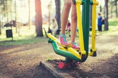 Adolescente que hace ejercicios en el simulador en parque Foto de archivo