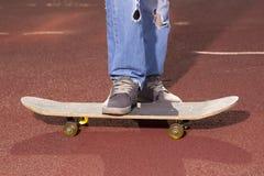 Adolescente que hace ejercicios en un monopatín Fotos de archivo