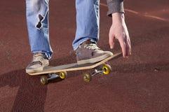 Adolescente que hace ejercicios en un monopatín Fotografía de archivo libre de regalías