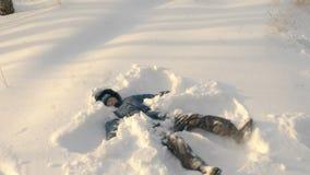 Adolescente que hace el ángel de la nieve que se acuesta en nieve almacen de video