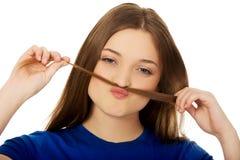 Adolescente que hace el bigote del pelo Foto de archivo