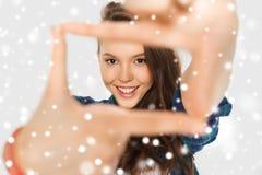 Adolescente que hace el marco de fingeres sobre nieve Imagenes de archivo