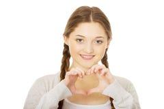 Adolescente que hace forma del corazón con las manos Fotografía de archivo libre de regalías