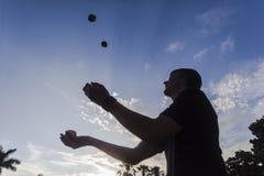 Adolescente que hace juegos malabares silueteado Imagen de archivo libre de regalías