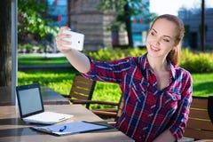 Adolescente que hace la foto del selfie con el teléfono elegante en parque Imagenes de archivo
