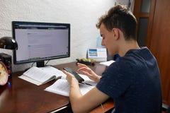 Adolescente que hace la preparación con el ordenador Fotos de archivo