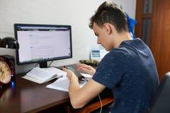 Adolescente que hace la preparación con el ordenador Foto de archivo