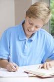 Adolescente que hace la preparación en la tabla Imagen de archivo libre de regalías