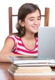 Adolescente que hace la preparación o que hojea el web en su ordenador portátil Fotografía de archivo libre de regalías