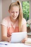 Adolescente que hace la preparación usando la tableta de Digitaces Foto de archivo libre de regalías