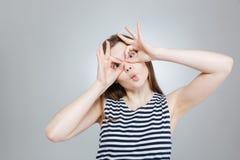 Adolescente que hace los vidrios por las manos y que muestra la cara divertida Fotos de archivo libres de regalías