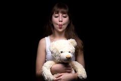 Adolescente que hace muecas con el oso de peluche Fotografía de archivo
