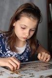 Adolescente que hace rompecabezas Imagenes de archivo
