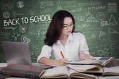 Adolescente que hace tarea de la escuela en clase Fotografía de archivo