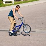 Adolescente que hace trucos en una bici de BMX Fotografía de archivo libre de regalías