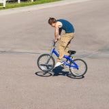 Adolescente que hace trucos en una bici de BMX Imagen de archivo libre de regalías