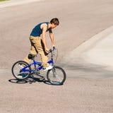 Adolescente que hace trucos en una bici de BMX Imagenes de archivo