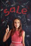Adolescente que hace un aviso grande de la venta que se coloca en el blac Fotos de archivo libres de regalías