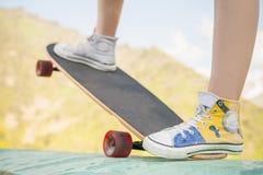 Adolescente que hace un truco por el monopatín al aire libre en la montaña Imagenes de archivo