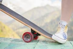 Adolescente que hace un truco por el monopatín al aire libre en la montaña Fotografía de archivo