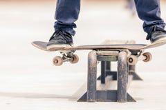 Adolescente que hace un truco por el monopatín en un carril en parque del patín Imagen de archivo