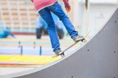 Adolescente que hace un truco por el monopatín en un golpeador en parque del patín Imagenes de archivo