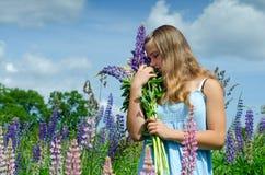 Adolescente que huele las flores Fotos de archivo