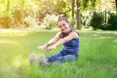 Adolescente que intenta tocar los pies con sus manos Foto de archivo