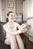 Adolescente que joga em um jogo do console Fotografia de Stock Royalty Free