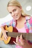 Adolescente que joga a guitarra acústica Fotografia de Stock Royalty Free