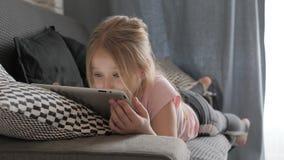 Adolescente que joga no PC da tabuleta que descansa em um sof? em casa Conceito dos povos, da tecnologia e do lazer vídeos de arquivo