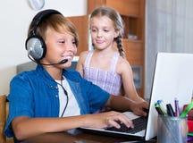 Adolescente que juega al juego online con la hermana Fotografía de archivo
