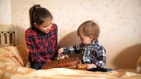 Adolescente que juega con el niño pequeño en cama en el dormitorio Fotos de archivo