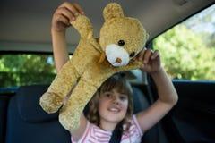 Adolescente que juega con el oso de peluche en el asiento trasero del coche Fotos de archivo