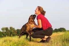 Adolescente que juega con el perro del boxeador Fotografía de archivo libre de regalías