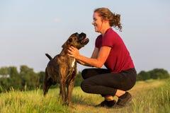 Adolescente que juega con el perro del boxeador Imagen de archivo