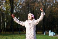 Adolescente que juega con las hojas otoñales Fotografía de archivo libre de regalías
